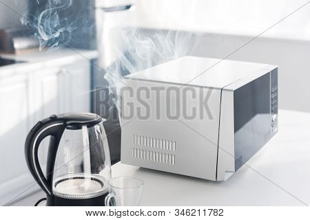 Electric Kettle, Broken And Steamy Microwave On Table In Kitchen