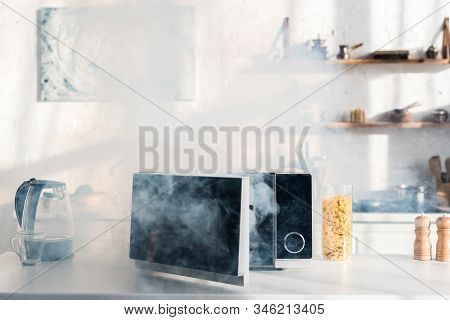 Electric Kettle, Pasta, Broken And Steamy Microwave On Table In Kitchen