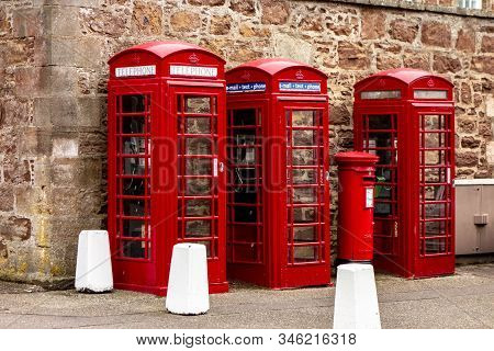 Three Typical British Red Phone Booths Near Fort George Barracks In Scotland
