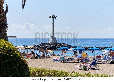 Tenerife, Spain - October 13, 2019: People Sunbathing On Sandy Beach Of Playa De Los Cristianos, Enj
