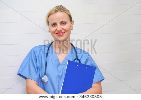 Doctor, Nurse With Stethoscope And Folder In Hand In Hospital. Doctor Or Nurse Holding A Folder Of I