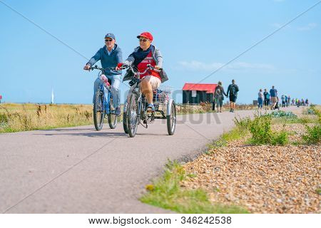 Rye England - August 20 2019;  Two Cyclists On Track With Famous Black Shed With Red Roof On Rye Nat