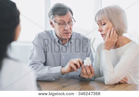 Prescription Medication. Confident Senior Man Pointing At Bottle, Reading Instructions, Asking Docto