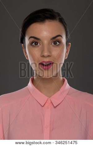 A Young Woman Of 30-35 Years Old In A Pink Blouse On A Gray Background, Restrained Emotions. Maybe S