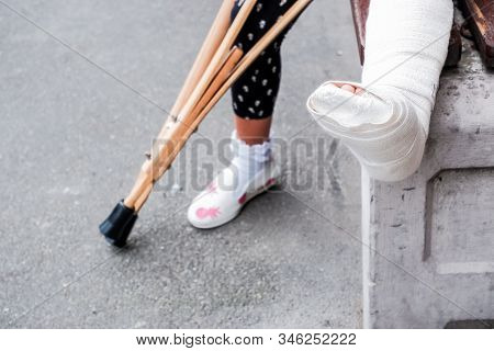 Child Using Crutches And Broken Legs For Walking, An Accident During Jumps. Broken Leg, Wooden Crutc
