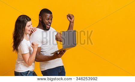 Online Credit. Happy Interracial Spouses Celebrating Win With Laptop, Raising Fists In Excitement, E