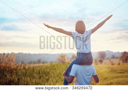 Portrait Of Young Man Holding On Shoulders His Happy Girlfriend, She Spread Apart Arms Mimicking Air