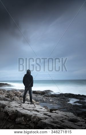 Silhouette Scene Of A Hooded Man Who Looks Like A Fighter, Dressed In Black In A Cove, Looking At Th