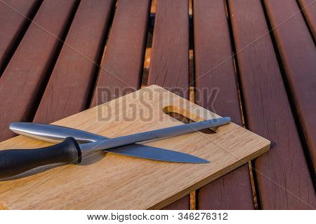 Steak Knife And Honing Steel On Woodblock Cutting Board On Picnic Table.