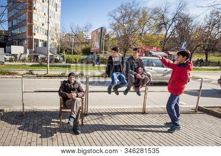 Prishtina, Kosovo - November 13, 2016: Old Man, Senior Retired, Sitting Next To A Group Of Youngster