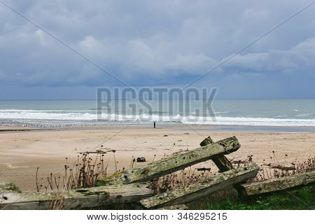 Photo Of A Person On A Sandy Beach With Waves Rolling In And Dramatic Sky Background, Taken At San G
