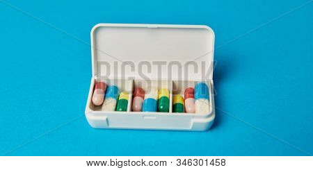 Open pill box with pills and capsules as medicine