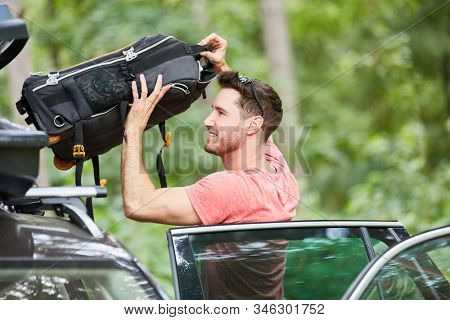 Man at the suitcase stowing in the car roof box before going on vacation