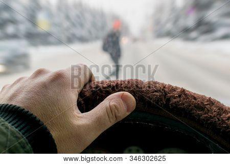 Emergency. A Man Hand On The Steering Wheel Of A Car While Braking Against The Background Of A Pedes