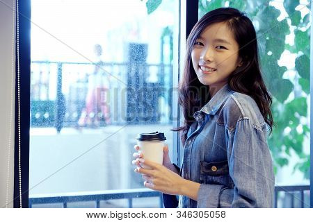 Asian Woman With Take Away Coffee Cup, Happy Asia Girl Looking At Camera And Holding Coffee While St