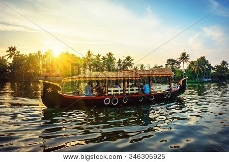 Traditional Indian Boat In Kerala, Tourists Relax On A Boat In The Evening Against The Backdrop Of A