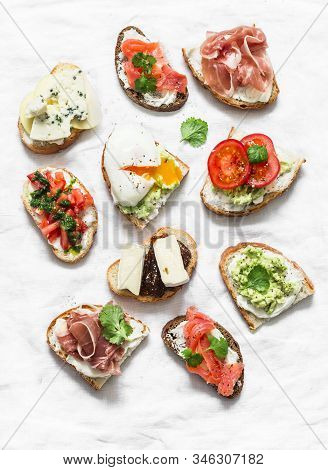 Variety Of Tapas Sandwiches  - Sandwiches With Prosciutto, Avocado, Salmon, Egg, Tomatoes, Jamon, Go
