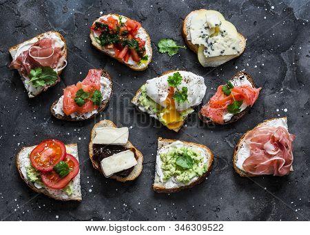 Variety Of Tapas Sandwiches With Prosciutto, Avocado, Salmon, Egg, Tomatoes, Jamon, Gorgonzola, Brie