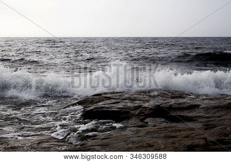 Breaking Waves In A Stormy Sea. The Sea Hit The Rocky Shore.