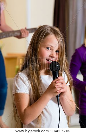 Children - three sisters - playing in a band making music, focus on girl with microphone in front