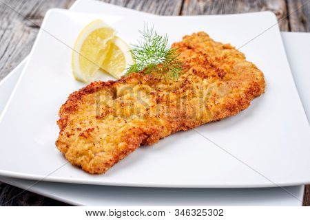 Traditional deep fried Wiener schnitzel from veal topside with lemon slice and herb offered as closeup modern design plate