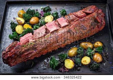 Barbecue dry aged venison tenderloin fillet steak and saddle natural with kalette and fried potatoes offered as closeup on a rustic board