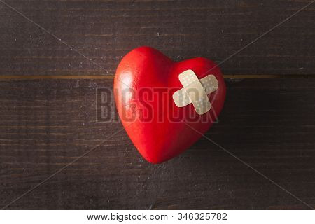 Red Broken Heart With A Band Aid On A Wooden Background