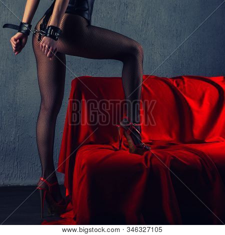 Beautiful Sexy Lady In Bdsm Outfit. Close Up Of Model With Hand In Bondage Near Red Sofa - Toned Ima