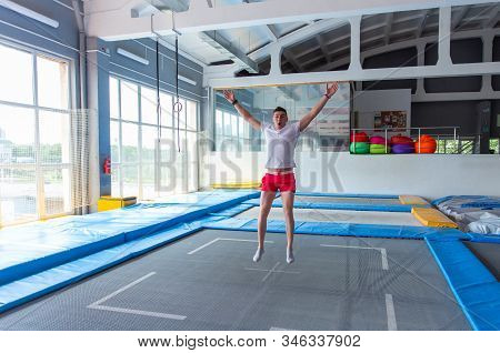 Fitness, Fun, Leisure And Sport Activity Concept - Handsome Happy Man Jumping On A Trampoline Indoor