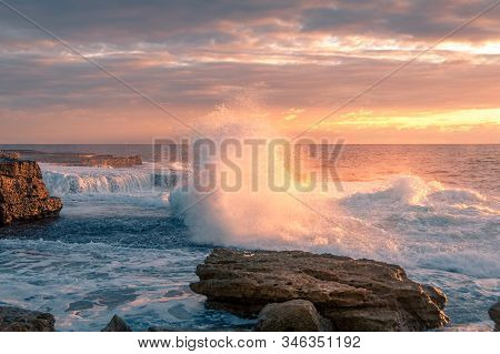 Huge Wave Crushing Over Rock With Splashes Of White Foam At Sunrise. Ocean Coastline Scene With Wave