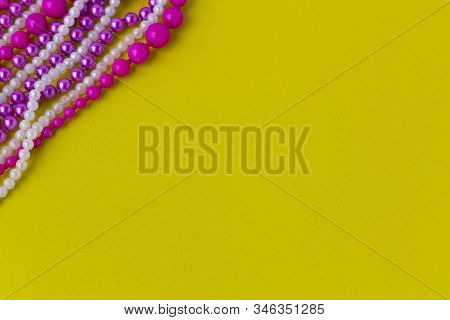 Mardi Gras Or Fat Tuesday Composition. Multi Colored Mardi Gras Beads And  On Yellow Background. Fla