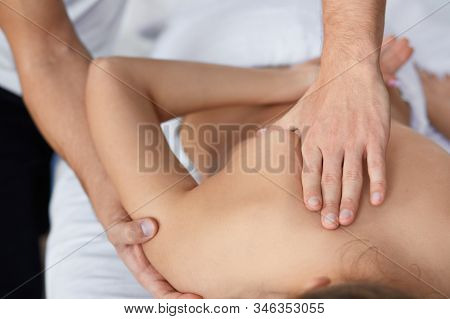 Young Beautiful Woman Enjoying Back And Shouders Massage In Spa.professional Massage Therapist Is Tr