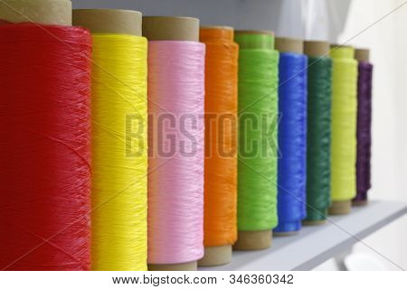 Large Tubes With Colored Threads. Sewing Production. Rows Of Spools Of Thread Of Different Colors In