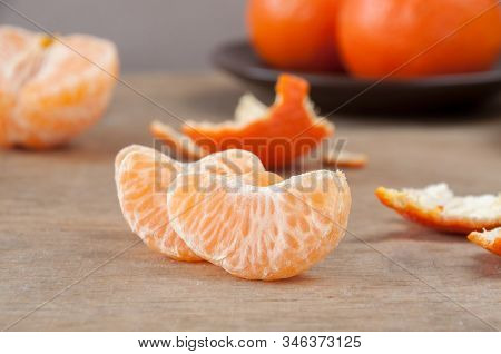 Slices Of Ripe Mandarin(tangerine) On A Wooden Table Against The Background Of Whole Tangerines And