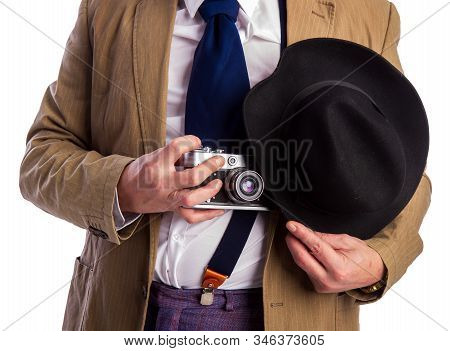 Retro Paparazzi In A Suit And Tie Secretly Takes A Photo On A Film Camera Hiding Behind A Hat