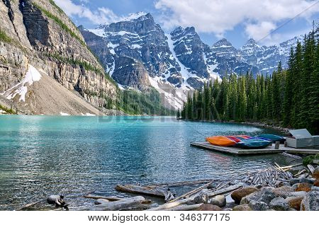 Turquoise Waters Of Beautiful Moraine Lake. Snow-covered Rocky Mountains In Summer Day. Canoes On A