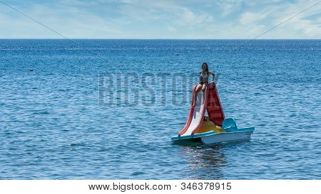 Teen In Bathing Suit Sitting On Paddleboat With Slide At Beach In Eressos, Lesvos Greece
