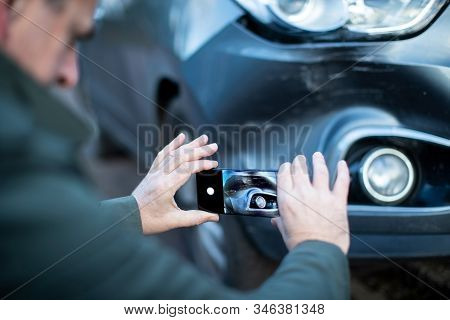 Male Driver Taking Photo Of Damaged Car After Accident For Insurance Claim On Mobile Phone