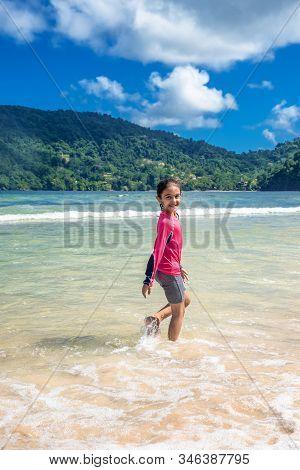 Little Girl Walking In Maracas Bay Beach Trinidad And Tobago Having Fun Splashing In The Waves Looki