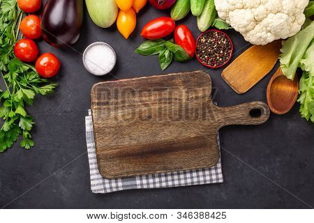 Brawn Cutting Board And Fresh Farmers Garden Vegetables On Stone Background. Harvest Time. Top View