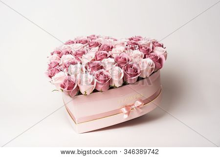 Flowers In Bloom: A Large Bouquet Of Pink And White Roses In A Box In The Shape Of A Heart On A Whit