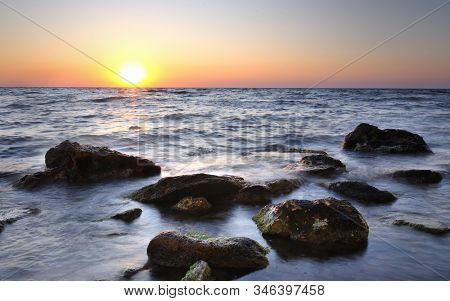 Beautiful Pink Sunset Over Still Sea Waters And Water Stones With Green Moss In Crimea