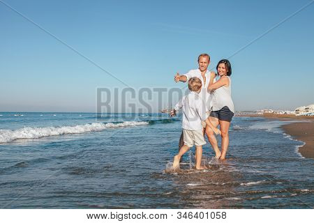 Father, Mother And Little Son Boy Have A Sea Walk Together On The Sea Surf Line In Side City, Turkey