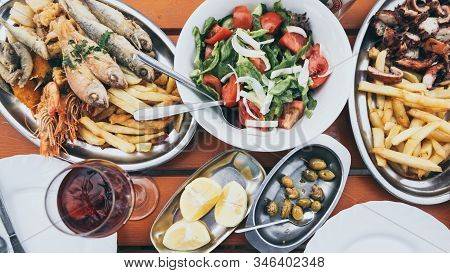 Flat Lay Of Cyprus Fish And Seafood Meze With Olives, Lemon And Greek Salad