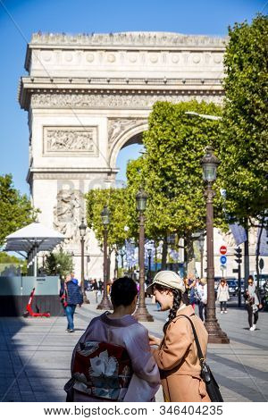 Paris/france - September 10, 2019 : Two Japanese Tourist Taking Pictures In Front Of The Arc De Trio