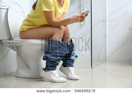 Woman With Smartphone Sitting On Toilet Bowl In Bathroom, Closeup