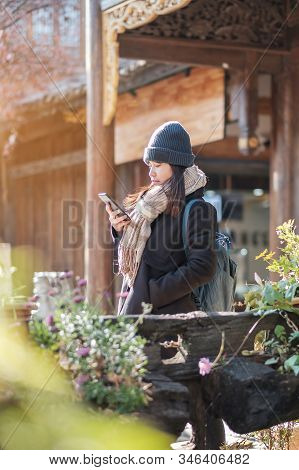 Happy Young Woman Traveler Using Mobile Phone Or Shelfie Photography At Lijiang Old Town, Landmark F