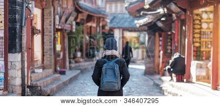 Young Woman Traveler Traveling At The Square Street In Lijiang Old Town, Landmark And Popular Spot F