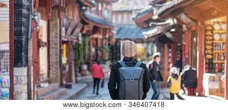 Young Man Traveler Traveling At The Square Street In Lijiang Old Town, Landmark And Popular Spot For