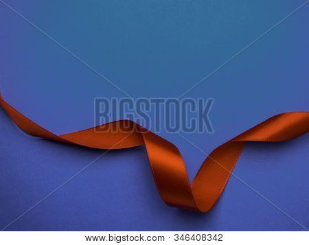 Red Silk Ribbon Twisted On A Trendy Classic Blue Background, Festive Postcard, Copy Space